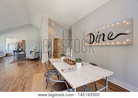 View Of Dining Table With Wooden Top And Metal Chairs.