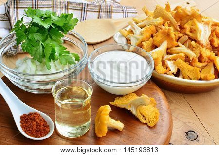 Chanterelle mushrooms with ingredients for cooking on the table