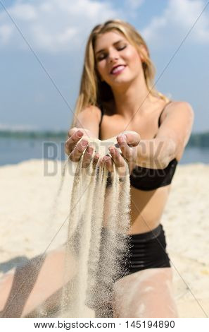 Young and happy model sow the sand trow her hands. Focus on the hands