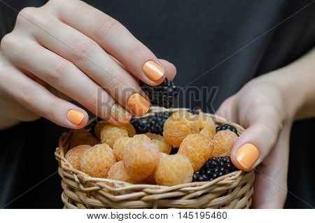 Female hand with yellow nail design holding a small basket with berries