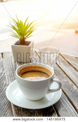 Smart phone and white coffee cup with glass water on wooden table.