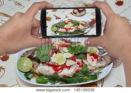 Using mobile phone to take photo a dish of Tilapia fish streamed lemon for share to social network. Selective focus
