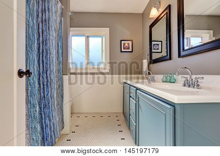 Interior Of Bathroom With Vintage Blue Vanity Cabinet And Two Sinks