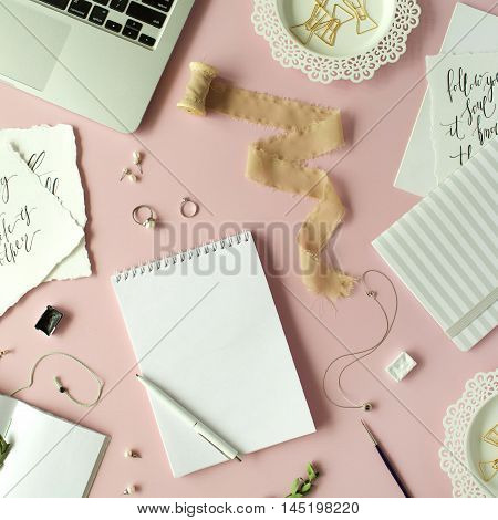 Flat lay top view office table desk. feminine desk workspace with laptop diary spool with ribbon calligraphy quotes and golden clips on pink background.