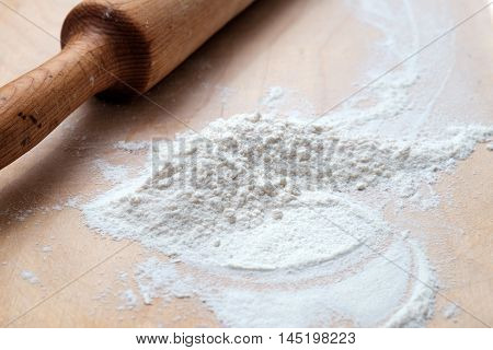 Wooden Rolling Pin With Flour On Wooden Desk
