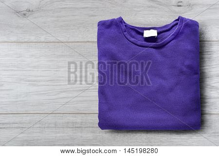 Folded purple sweatshirt on white wooden background