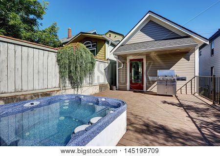 Wooden Walkout Deck With Hot Tub And Barbecue