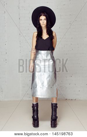 Confident girl holding all in her hands and control of all. Model in the studio posing to the photograther with black hat near grey brick wall. She is sad