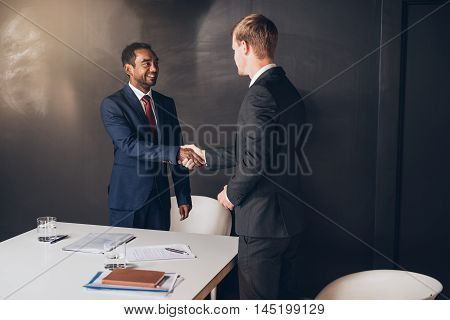 Two young businessmen standing in a modern boardroom shaking hands together after a successful negotiation