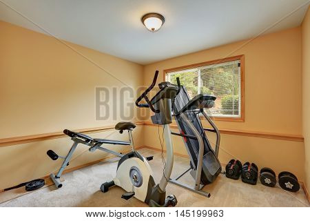 Small Gym Room With Exercise Equipments.