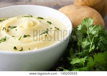 Mashed potato in white bowl on wooden table