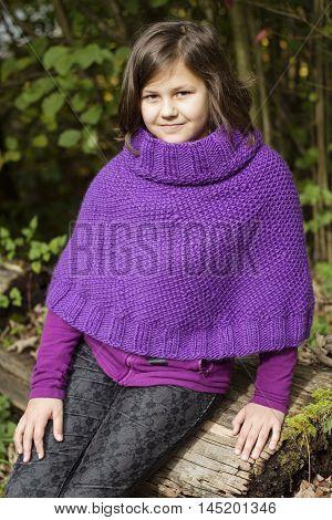 the portrait of a teenage girl wearing purple poncho