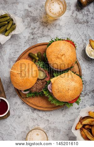 Three fresh homemade different hamburgers on round wooden board on light gray surface with lager top view