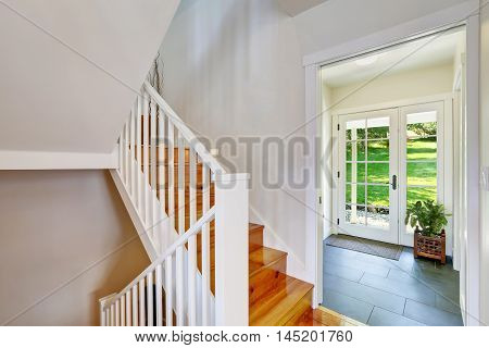 Bright White Hallway Interior With Wooden Staircase