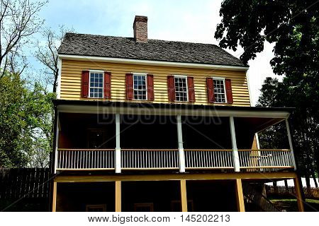 Old Salem North Carolina - April 21 2016: Early 19th century wood frame Main Street house with front porch and central chimney