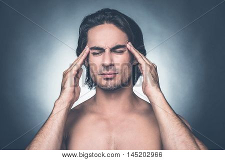 Feeling that awful headache. Portrait of frustrated young shirtless man keeping eyes closed and touching head with fingers while standing against grey background