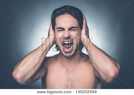 Too loud sound. Portrait of frustrated young shirtless man keeping eyes closed and covering ears with hands while standing against grey background