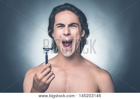 Bad razor. Young shirtless man holding razor and expressing negativity while standing against grey background