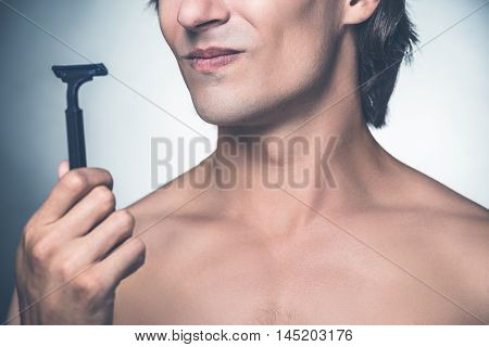 Need a new razor? Close-up of young shirtless man holding razor and expressing negativity while standing against grey background