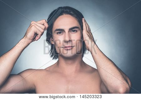 Used to look perfect. Portrait of young shirtless man combing his hair with hairbrush and looking at camera while standing against grey background