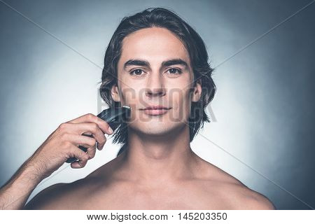 Safe shaving. Handsome young shirtless man shaving with electric razor and looking at camera while standing against grey background