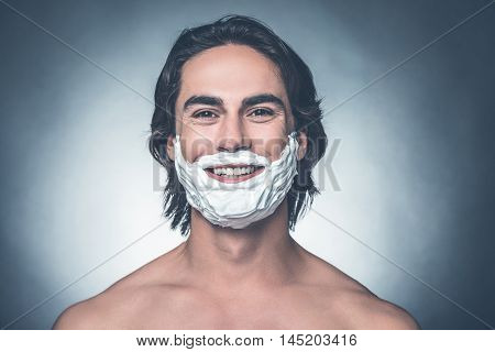 Ready for morning shave. Portrait of young shirtless man with shaving cream on face looking at camera and smiling while standing against grey background