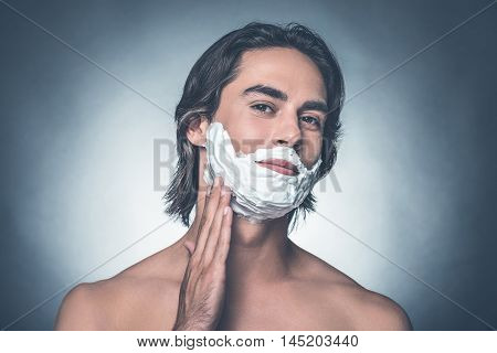 Comfortable shaving. Handsome young shirtless man spreading shaving cream over face and looking at camera while standing against grey background