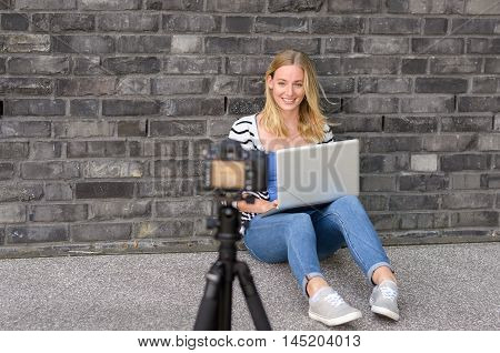 Cute Blond Female Blogger With Laptop Recording Video