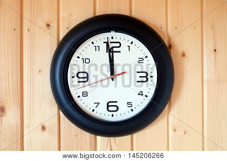 Big round wall clock with a black rim with arrows showing twelve o'clock hangs on brown wooden wall from vertical planks horizontal view indoor close-up