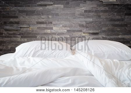White Bedding Sheets And Pillow On Natural Stone Wall Room Background, Messy Bed Concept