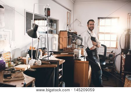 Portrait of a smiling young jeweler standing in a workshop full of tools and jewelry making equipment