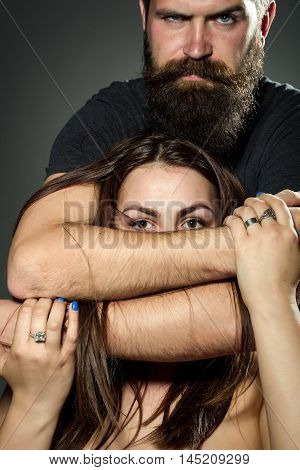 Handsome bearded man with serious face embracing young woman topless in studio on grey background