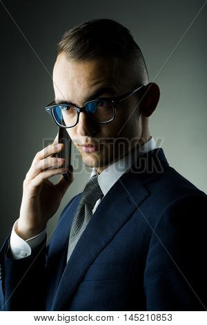 young fashion businessman with nerd glasses on emotional face and stylish hairdo in jacket speaking on mobile phone posing on grey background