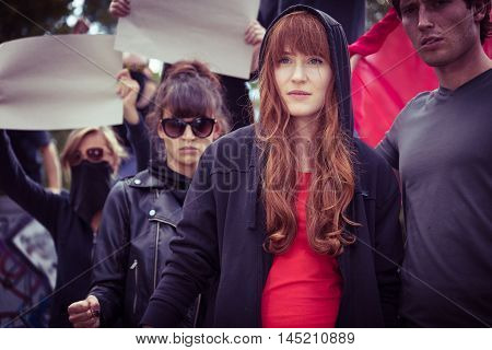 Passionate young woman in a hoodie taking part in a street protest