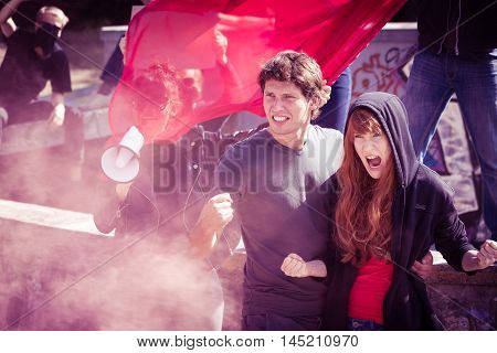 Rebellious couple shouting and raising fists in the middle of a demonstration