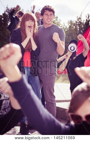 Young couple with scared faces participating in a protest rally