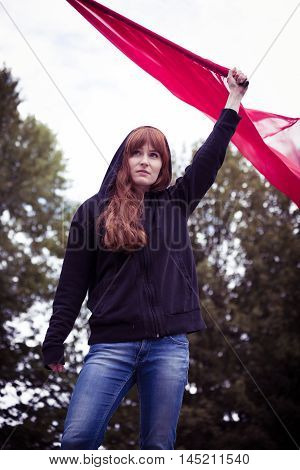 Determined young woman in a hoodie holding a flag in a rebellious manner
