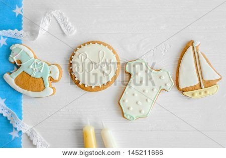 Baby cookies decorated with glaze on light wooden background