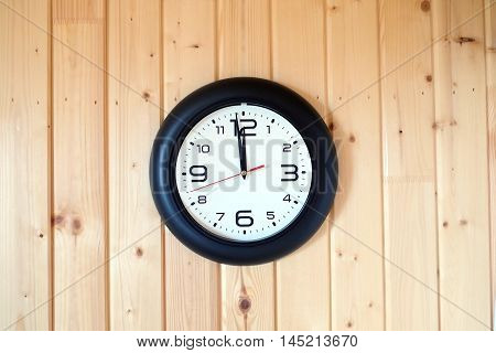 Big round wall clock with a black rim with arrows showing twelve o'clock hangs on brown wooden wall from vertical planks horizontal view indoor on wooden background