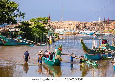 HIKKADUWA NOVEMBER 27 : Fisherman's with boat at the marina on November 27 2015 in Hikkaduwa Sri Lanka