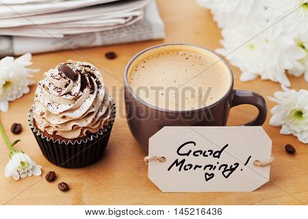 Coffee mug with cupcake, notebook and pencil on rustic table from above. Cozy and sweet breakfast. Good morning or have a nice day concept. Flat lay.