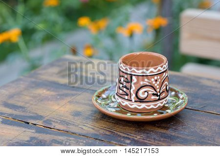 Traditional wine clay glass with ornaments on a restaurant table in Moldova