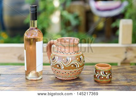 Rose wine bottle and traditional jag with ornaments on a restaurant table in Moldova