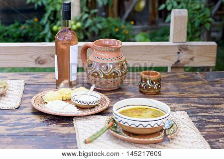 Rose wine bottle and traditional jag with ornaments, national food on a restaurant table in Moldova