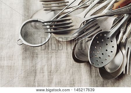 Vintage cutlery on rustic background. Old kitchen tools, retro colors.