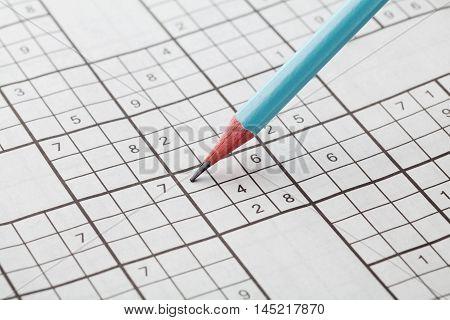 Crossword sudoku and blue pencil for entertainment, popular conundrum.