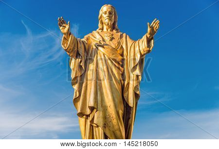 Old Jesus Christ Golden Statue Isolated Over Blue Sky