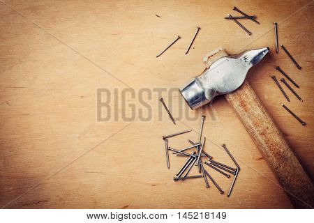 Old hammer and nails on wooden rustic background, working tools, top view.