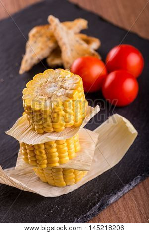 Corn With Bread And Tomatoes On Slate Stone