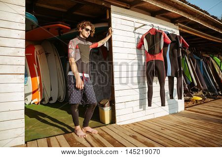 Young handsome curly man in swimsuit and eyeglasses standing at the surf shack at the beach